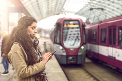 Woman at station with approaching train Stock Images