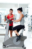 Woman on stationary bicycle with personal trainer. At  fitness gym Stock Photography
