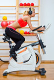 Woman on stationary speed bike Stock Photo