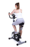 Woman on stationary training bicycle Stock Images