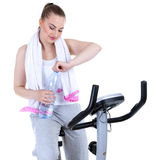 Woman on stationary training bicycle Stock Photography