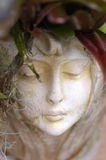 Woman statue face. Closeup of the face of a carved woman's face with flora for hair Stock Images