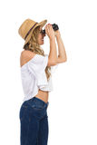 Woman In Staw Hat Observe. Blond young woman in straw hat, jeans and white shirt is looking through binoculars. Side view. Three quarter length studio shot Stock Photo