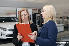 Woman stay a car insurance policy, the agent is pointing at the document. Woman stay a car insurance policy, the agent is pointing Stock Photo