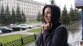 A woman stay on the street and freezes. It`s raining stock video footage
