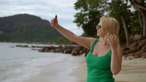 Woman staying on a beach and taking selfie stock video footage