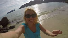 Woman staying on a beach and taking selfie stock footage