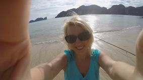 Woman staying on a beach and taking selfie stock video