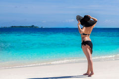 Woman is staying on the beach and watching over the sea Stock Photo