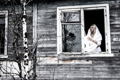 Woman staying near the broken window Stock Images