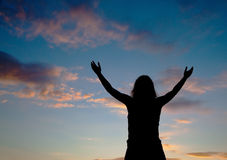 Woman staying with raised hands. At the sunset time Royalty Free Stock Image
