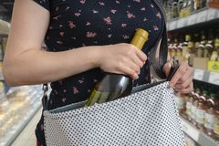 Woman is stealing bottle of wine and hiding it in handbag in supermarket stock photos