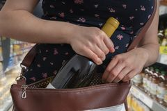 Woman is stealing bottle of wine and hiding it in handbag in supermarket royalty free stock photo