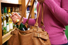 Woman Stealing Bottle Of Wine From Supermarket Stock Photos