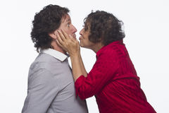 Woman stealing a kiss from man, horizontal Royalty Free Stock Image