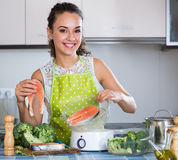 Woman steaming salmon and vegetables Stock Photos