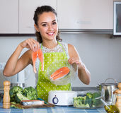 Woman steaming salmon and vegetables royalty free stock photos