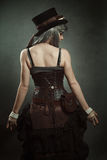 Woman with steampunk dress. Woman back. Steampunk dress and texture stock photography