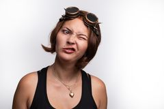 Woman with steampunk glasses displaying twisted crazy expression. Shot against white background royalty free stock photography