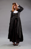 Woman steampunk glasses. Redhead woman with long red hair wearing steampunk glasses, a black dress and white blouse on a grey background stock photos