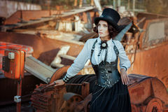 Woman in steampunk style. Woman dressed in a suit and a hat in a steampunk style stands next to the machines stock photos