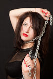 Woman and a steel chain. Beautiful young woman with a chain around his neck on a black background royalty free stock photo