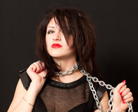 Woman and a steel chain. Beautiful young woman with a chain around his neck on a black background royalty free stock image