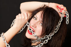 Woman and a steel chain. Beautiful young woman with a chain around his neck on a black background royalty free stock photography