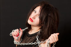 Woman and a steel chain. Seductive young woman holding a steel chain on a black background royalty free stock image