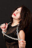 Woman and a steel chain. Seductive young woman holding a steel chain on a black background stock images