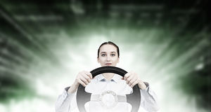 Woman with steering wheel. Young smiling pretty woman driving steering wheel Royalty Free Stock Photo
