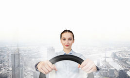Woman with steering wheel. Young smiling pretty woman driving steering wheel Stock Photography