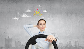 Woman with steering wheel. Young smiling pretty woman driving steering wheel Stock Photo
