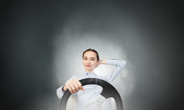 Woman with steering wheel. Young smiling pretty woman driving steering wheel Stock Image