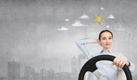 Woman with steering wheel. Young smiling pretty woman driving steering wheel Royalty Free Stock Photos