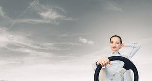 Woman with steering wheel. Young smiling pretty woman driving steering wheel Royalty Free Stock Images