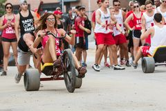 Woman Steers Adult Big Wheel In Atlanta Field Day Race. Atlanta, GA, USA - July 14, 2018: A young woman gets a push at the start line as she begins her leg of stock images