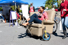 Woman Steers Oddball Furniture Piece On Wheels At Unique Fair Stock Images