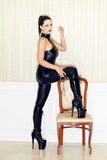 Woman step on chair in latex boots Royalty Free Stock Image