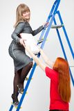 A woman on a stepladder with papers Stock Photo