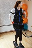 Woman on stepper. Caucasian woman in gym training on stepper with weights. She wears electric muscle stimulation suit, purposed to increase effectiveness of Royalty Free Stock Photos
