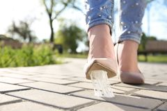 Woman stepping in chewing gum on sidewalk. Concept of stickiness Royalty Free Stock Photo