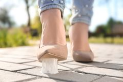 Woman stepping in chewing gum on sidewalk. Concept of stickiness Royalty Free Stock Photos