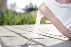 Woman stepping in chewing gum on sidewalk. Concept of stickiness Stock Image