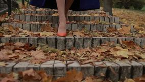 Woman stepping down on stairway in city at fall stock video footage