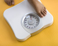 Woman Stepping On Scale Stock Photo