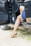 Woman stepping out of the car Stock Photos