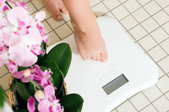Woman stepping on scale. Woman (only feet to be seen) stepping on a scale in a spa setting Stock Photos