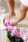 Woman stepping on scale. Woman (only feet to be seen) stepping on a scale in a spa setting Royalty Free Stock Photography