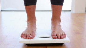 Woman stepping on scales. At the gym stock video footage